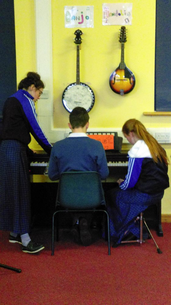 Desmond College Students Collaborating Around the Piano in Music Class