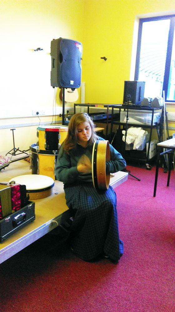 Desmond College Student playing the bodhrán during Music Class