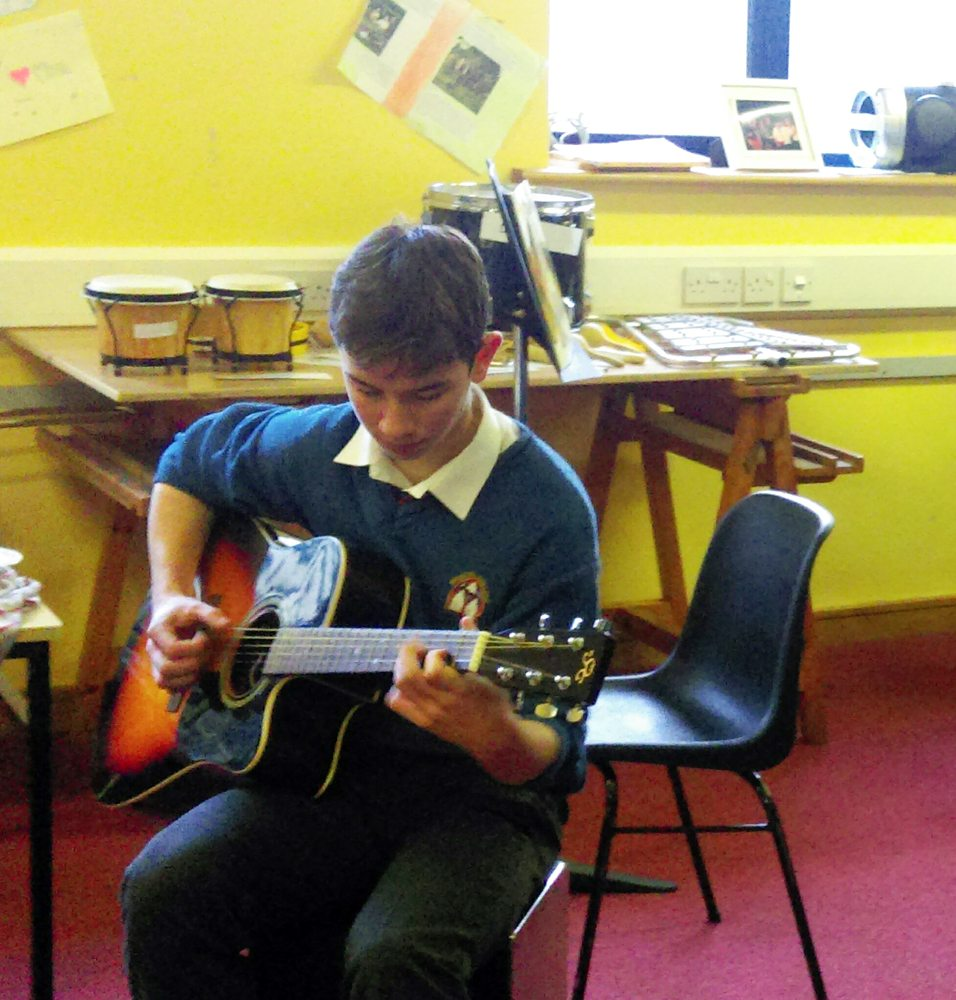 Desmond College Student strumming a guitar during Music Class