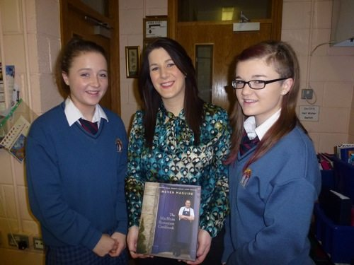 Students who participated in Neven Maguire's cooking demonstration present his book to Home Economics teacher