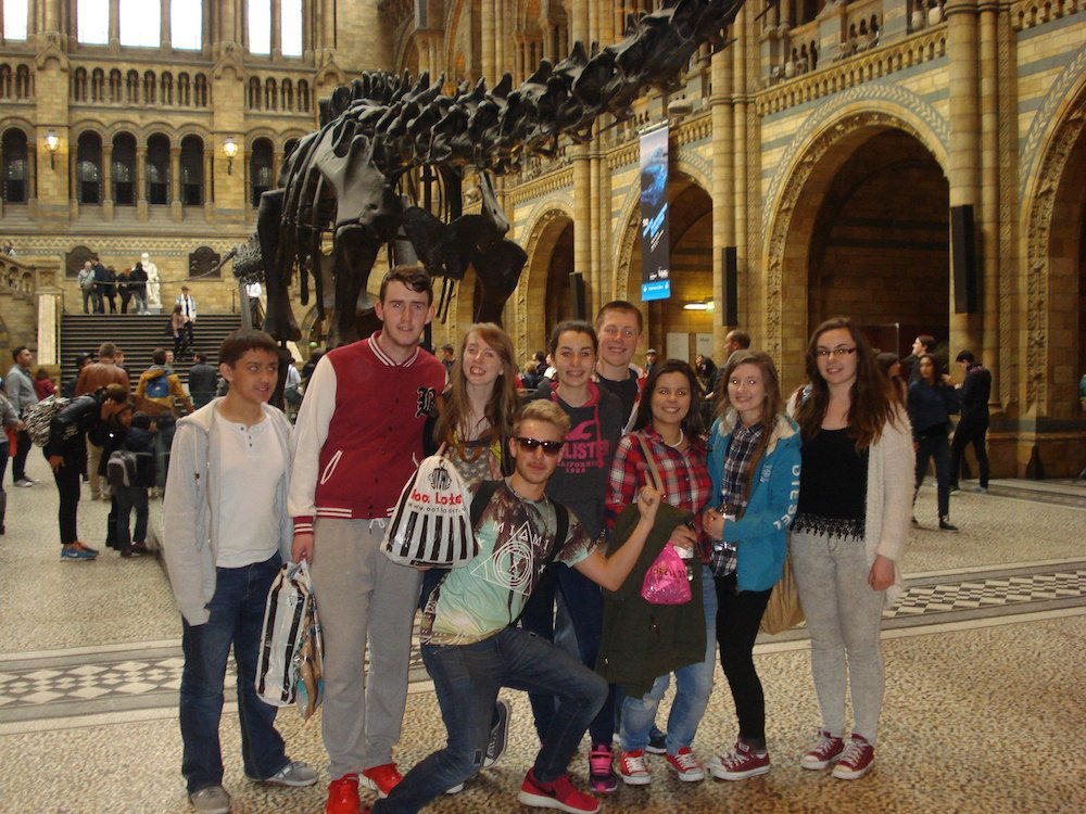 Matthew Hally, Liam Dowling, Orla Wren, Killian Begley, Stacey Flynn, Sean McElliggot, Lauren Moloney, Sara Flatley and Chloe Collins with a dinosaur at London Natural History Museum on their Transition Year School Trip to London