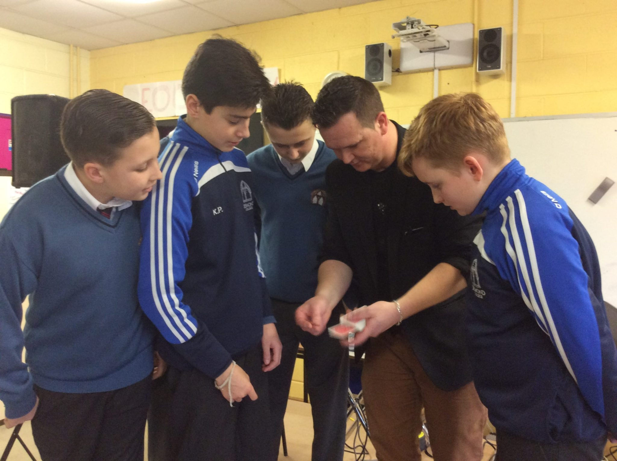 Jan 2016: Mike Nash, Konrad Papierowski, Corey Healy and AJ O Donovan watching intently as Magician Leon show them one of his amazing card tricks during Numeracy week in Desmond College