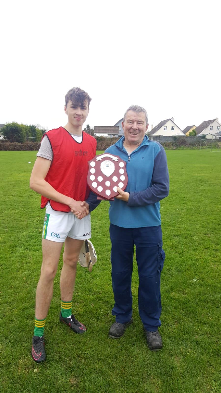 Nov 2018: Tiernan Mason receiving the winning shield from John English